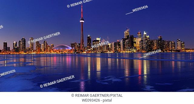 Panorama of frozen ice covered Lake Ontario reflecting the lights of Toronto city skyline at dusk