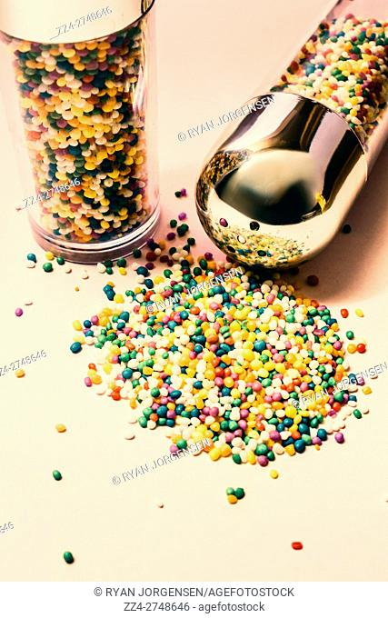 Shaker with spilt colorful hundreds and thousands, nonpareils or sugar candy pearls scattered on a white background with copy space