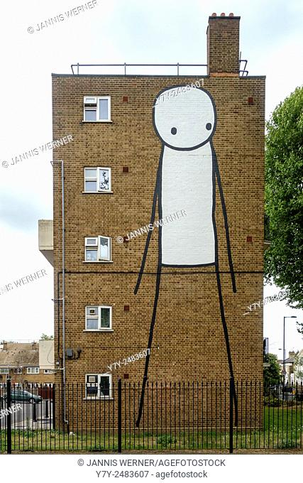 Urban art on a brownstone residential building in East London, UK