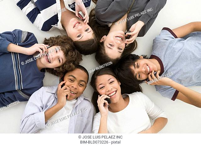 Teenage friends laying on floor talking on cell phones