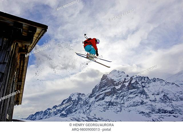 A young man skis off the roof of an alpine hut in Grindalwald, Switzerland