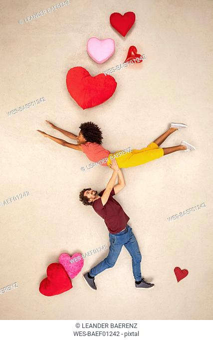 Happy couple with hearts around carrying each other