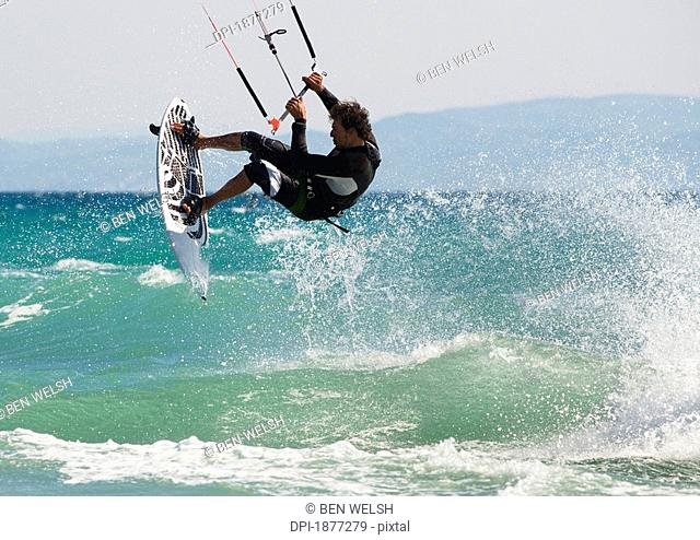 tarifa, cadiz, andalusia, spain, a man kitesurfing off dos mares beach in front of hotel dos mares