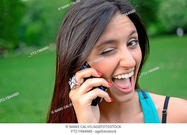 Attractive young mixed race woman talking on mobile phone in Central Park, New York City