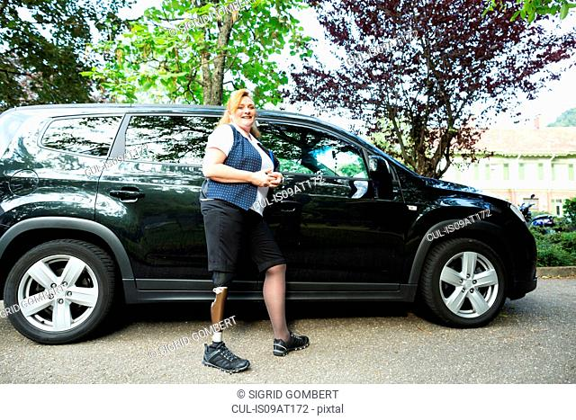 Portrait of mid adult woman with prosthetic leg, standing beside car