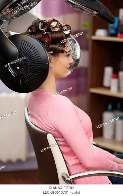 Young woman sitting under hair dryer with rollers. Debica, Poland