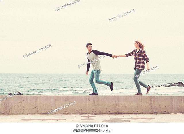 Young couple walking hand in hand by the sea