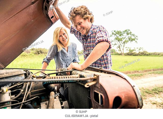 Young man and girlfriend checking jeep engine