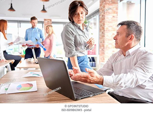 Colleagues in office with laptop having discussion