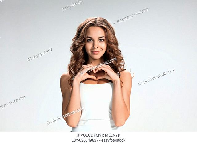 The young woman's portrait with love happy emotions on gray background
