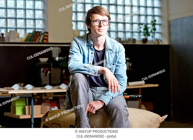 Coffee business owner sitting on sack of coffee beans
