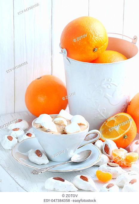 Coffee cappuccino with meringue and oranges on a white background