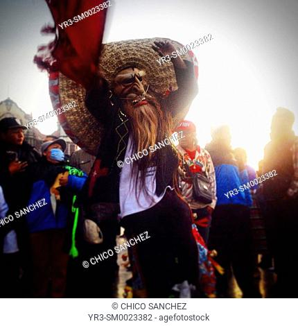 A man wearing a big sombrero and a mask with a beard dances during the annual pilgrimage to the Our Lady of Guadalupe basilica in Mexico City, Mexico