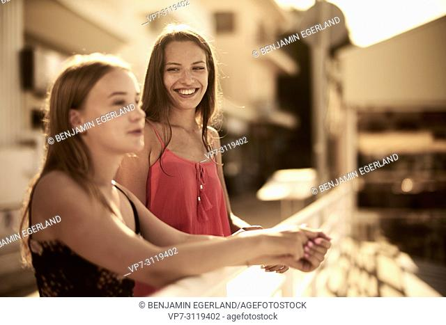 two women, best friends, leaning on handrail. In holiday destination Chersonissos, Crete, Greece
