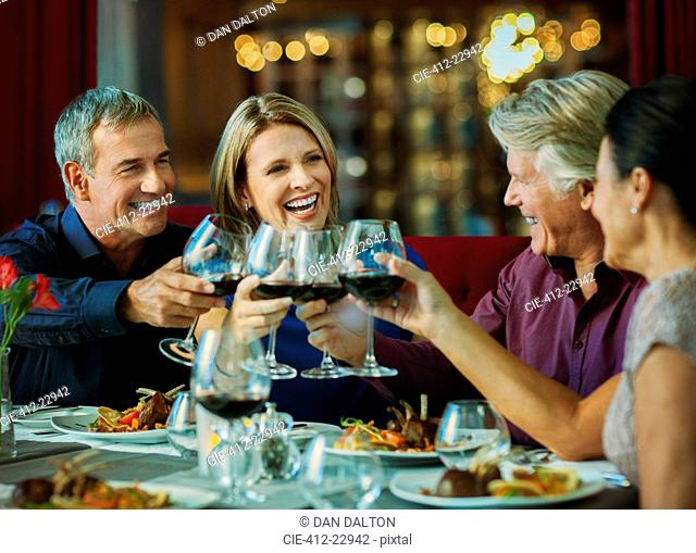People toasting with red wine in restaurant