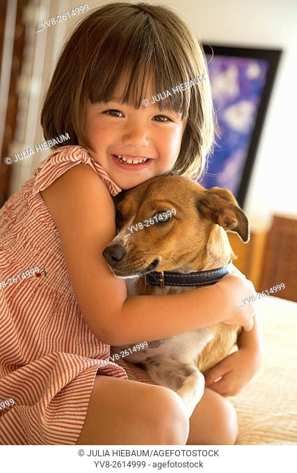 Toddler girl embracing her dog at home