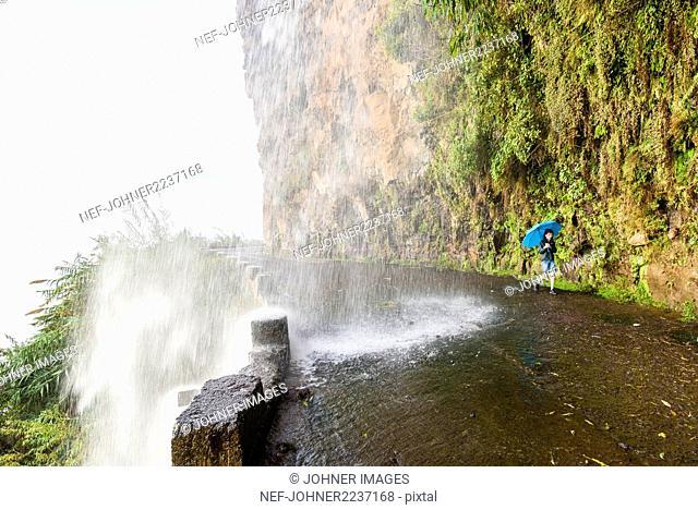 Boy with umbrella under waterfall