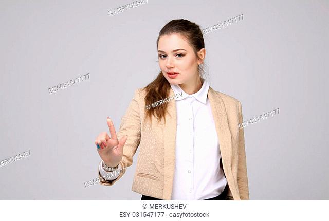 woman presses a virtual button, on grey background