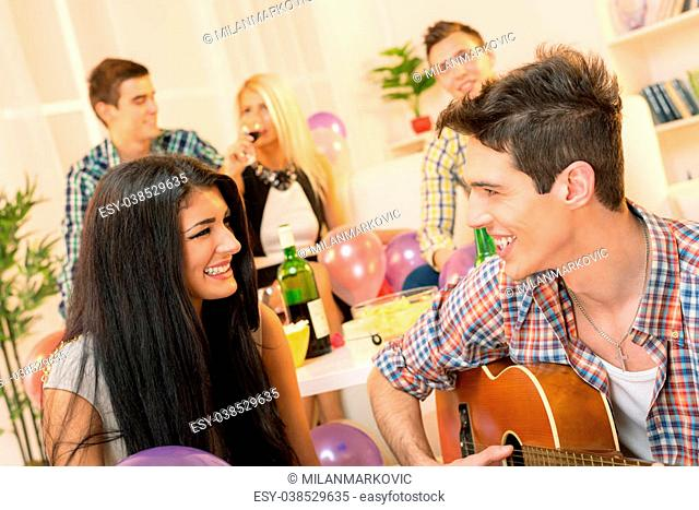 A young man with an acoustic guitar, at home party, courting a pretty girl playing to her. In the background you can see young people sitting on the couch and...