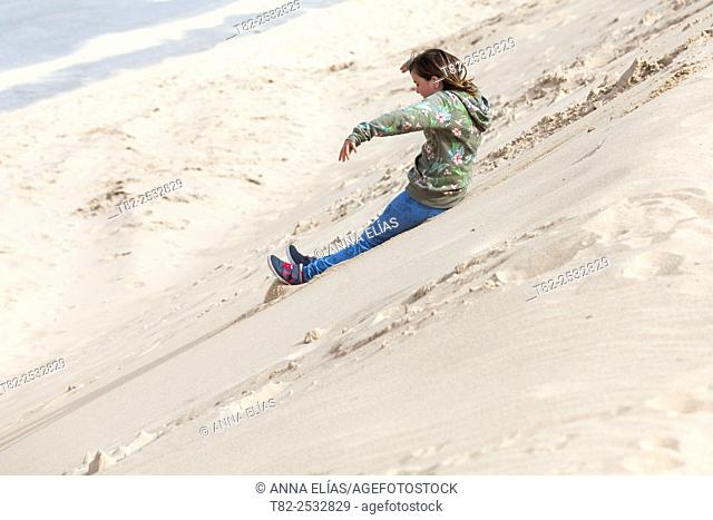 They slide down sand girl on the beach. Cadiz, Andalusia, europe