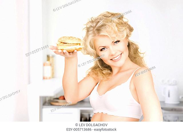 young beautiful woman with burger at home