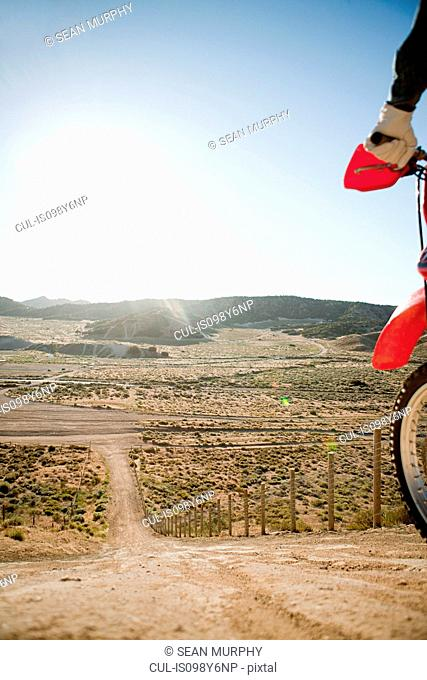Man with dirt bike on hill