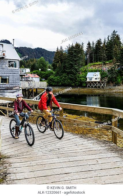 Mother and daughter bicycling on the historic oceanside boardwalk, Seldovia, Southcentral Alaska, USA