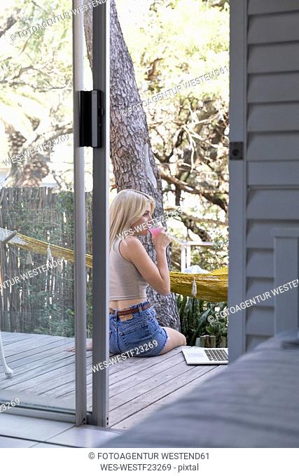 Young woman sitting on terrace with drink and laptop