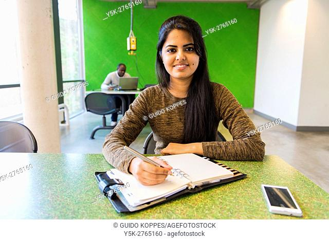 Aachen, Germany. Young, female Indian university exchange student working on a dormatory work desk, using her smartphone and analog notebook