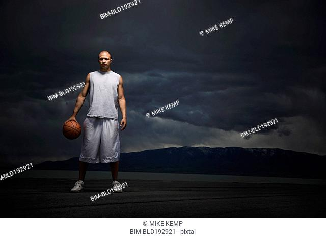 Mixed race basketball player standing with storm clouds in distance