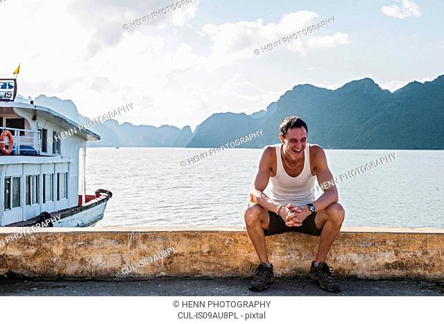 Man sitting at pier, Halong Bayy, Vietnam