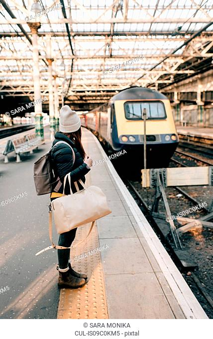 Woman waiting on platform in train station, Edinburgh, Scotland