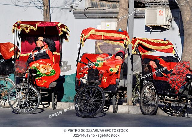 Beijing (China): rickshaw drivers waiting for clients and taking a nap by the Bell Tower