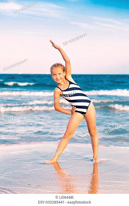 Beautiful little girl excercising on the beach outdoor