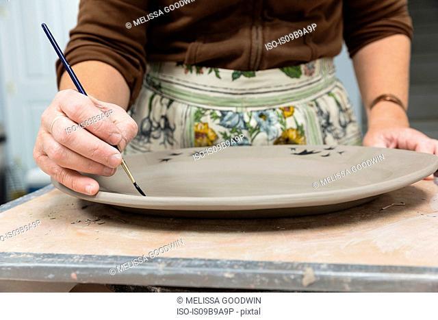 Potter painting motifs on platter