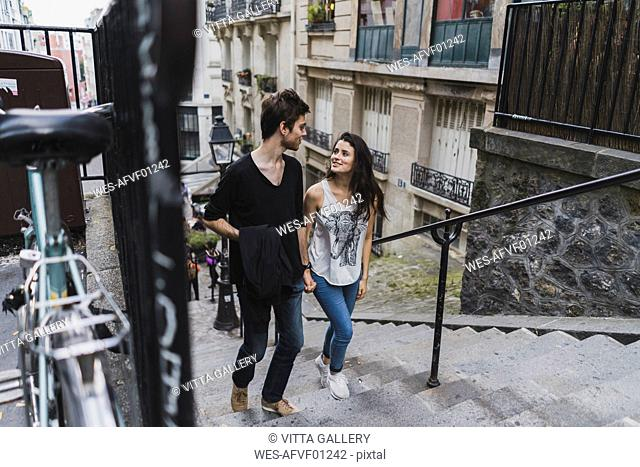 France, Paris, young couple walking in the district Montmartre