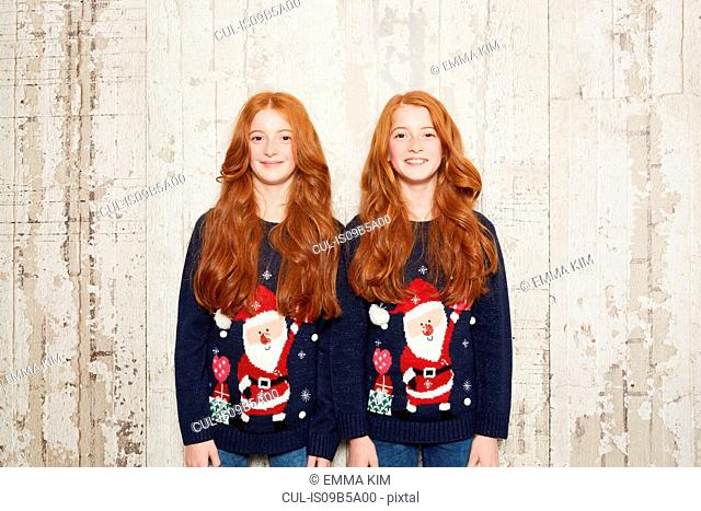 Portrait of twin sisters wearing Christmas jumpers