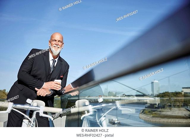 Elegant businessman with bicycle, standing in the city, teking a break