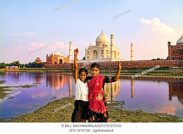 Young local children celebrating at World famous Taj Mahal at sunset from Yamuna River with reflection in town of Agra India