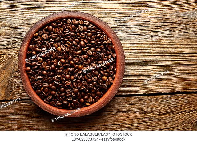 Coffee beans in a clay dish with nice texture on aged wood table background