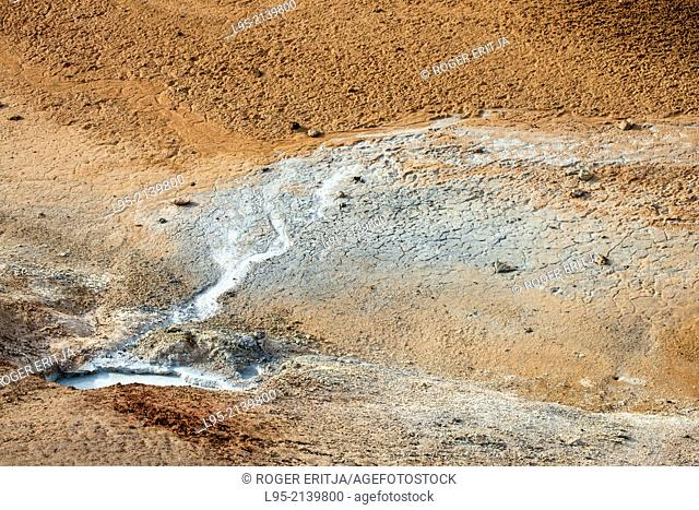 Hot water coming from undergound volcanic layers charged with Sulphur laying the mineral at the surface and forming sulphuric acid and foetid gases