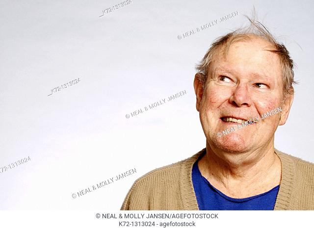 Elderly man with funny hairdo looking to the side