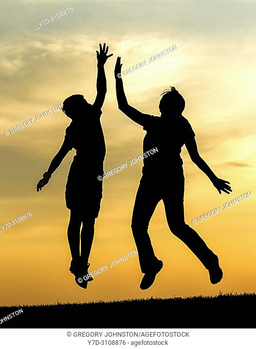 A boy and a teen girl jump up at sunset and give each other a high five