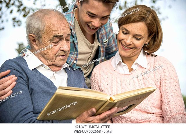 Senior man with grandson and daughter looking at photo album