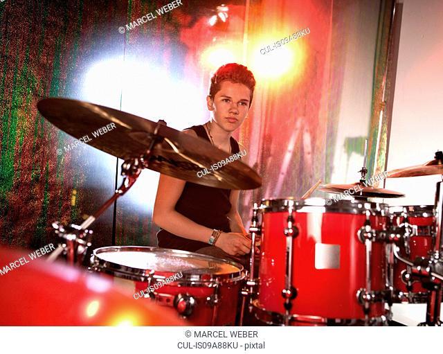 Teenage boy playing drum kit