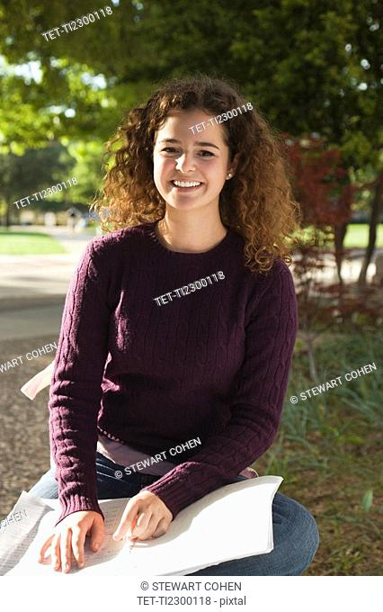 Teenage girl studying in the park