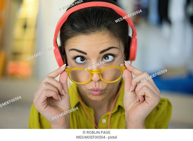Portrait of woman with headphones and glasses pulling funny face