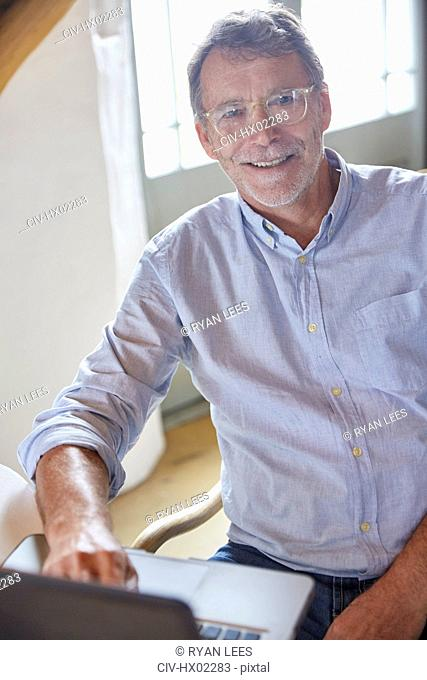 Portrait smiling senior man using laptop