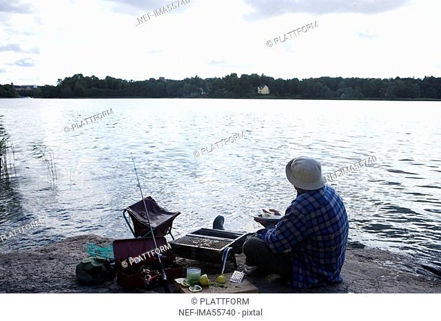 A man barbecuing fish by the water Sweden