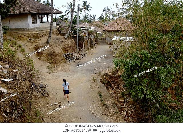 One Asian girl walking on a dirt road in a remote village